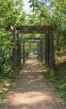 Wood arch above pathway in the park Stock Images