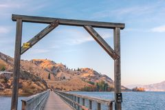 Wood archway over former train trestle bridge converted to walking and biking trail with lake and mountains in distance at sunset. Converted train trestle bridge Stock Photo