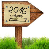 Wood arrow sign with 2016 loading handwritten on old page of pap. Er nailed to planks, green grass around, isolated on a white background Royalty Free Stock Photo