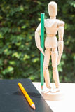 Wood artist mannequin standing with colour pencil Royalty Free Stock Photos