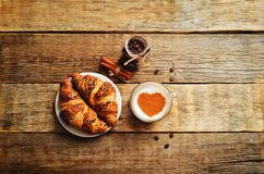 Wood background with cappuccino, croissants, cinnamon and jar of Stock Images