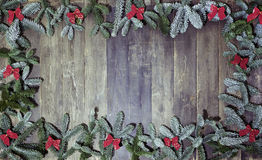 Wood background christmas loops. An old wooden background, decorated with pine branches and red loops, a Christmas background Royalty Free Stock Image