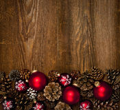 Wood background with Christmas ornaments. Rustic wood background with Christmas ornaments and pine cones royalty free stock photo