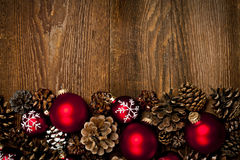 Wood background with Christmas ornaments. Rustic wood background with Christmas ornaments and pine cones stock photos