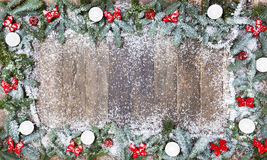 Wood background christmas snow. An old wooden background, decorated with pine branches, red loops and snow, a Christmas background Royalty Free Stock Image
