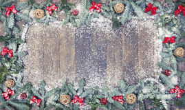 Wood background christmas wooden balls. An old wooden background, decorated with pine branches, red loops and snow, a Christmas background Royalty Free Stock Image