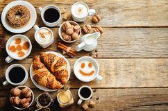 Wood background with different types of coffee and desserts to t Royalty Free Stock Photos