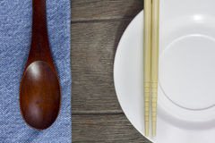 Wood background plates, chopsticks and spoons on blue jeans text Royalty Free Stock Photo
