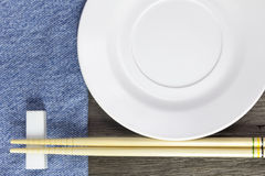 Wood background plates, chopsticks and spoons on blue jeans text Stock Images
