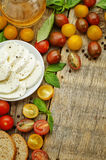Wood background with tomatoes, Basil, mozzarella, bread. Toning. selective focus Royalty Free Stock Photos