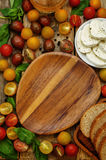 Wood background with tomatoes, Basil, mozzarella, bread. Toning. selective focus Stock Photos
