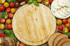 Wood background with tomatoes, Basil, mozzarella, bread. Toning. selective focus Stock Images
