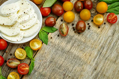 Wood background with tomatoes, Basil, mozzarella. Toning. selective focus Stock Photos