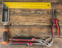 Wood background with tools like ruler pliers screwdriver.  Stock Photos
