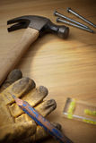 Wood Background With Tools. A still life with tools, gloves and level on a wood background Royalty Free Stock Photos