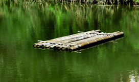 Wood bamboo boat on water Royalty Free Stock Image