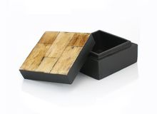 Wood and Bamboo Gift Box. Small Black wooden box with light wood tiles on top. Box is open and has reflection Stock Image