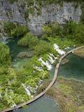 Wood bana och vattenfall i den Plitvice nationalparken royaltyfri bild