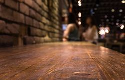 Wood bar table on cafe in dark night with people Stock Photography
