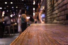 Wood bar table on cafe in dark night with people Royalty Free Stock Photos