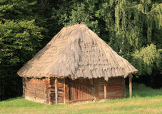 Wood barn. Old wood log shed with thatch roof on historical country homestead Royalty Free Stock Images