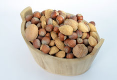 Wood basket full of nuts. Hazelnuts, walnuts and almonds in a wood basket  on white background Stock Images