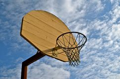 Wood Basketball Backboard. A well kept wood basketball backboard, hoop and net stand out against a clouded blue sky Royalty Free Stock Image