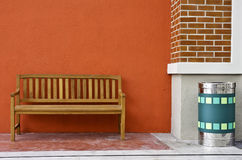 Wood Bench Against blank Wall and green trash. Stock Photography