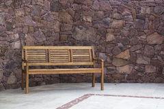 Wood bench. In front of stone wall Royalty Free Stock Photo