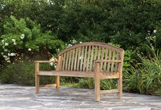Wood Bench in a garden. Teak bench on a stone patio in a flower garden Stock Image