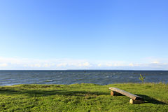 Wood bench on a grass at coast Royalty Free Stock Images