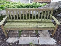 Wood bench with green lichen and stone tiles. Wood bench or seat with green lichen and stone tiles stock photo