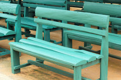 Wood bench green a lot Royalty Free Stock Image