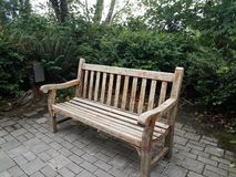 Wood bench or seat on stone tile and green plants stock images