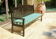 Wood Bench. With striped cushion displayed outdoors stock photo