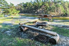 Wood bench, table and outdoor bbq. In a swedish lake surrounded by rocks and forest royalty free stock images