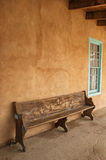 Wood bench beside teal trimmed window Royalty Free Stock Images