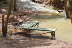 Wood bench water. Bamboo stream sunlight day royalty free stock photography