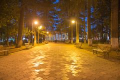 Wood benches and park alley. City night park in autumn with paths strewn Royalty Free Stock Photos