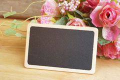 wood blackboard in front of artificial roses bouquet Royalty Free Stock Photos
