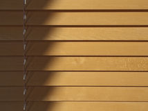 Wood blinds. Beechwood blinds in sunlight. Shadow and adjustment string on the left with diminishings shadows beneath the shutter strips Stock Image