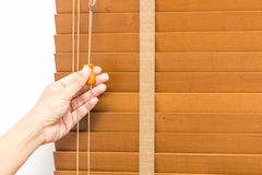 Wood blinds closed by hand. Hand pull closed wood blinds closed at windows stock photography
