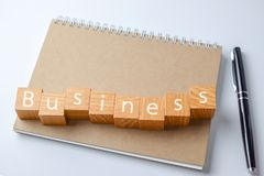 Wood block with business word on Notebook with pen. Business concept royalty free stock images