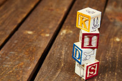 Wood Blocks. Four wood blocks  spelling the word kids over a darker wood texture Royalty Free Stock Image