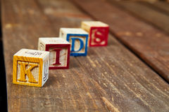 Wood Blocks. Four wood blocks  spelling the word kids over a wood texture Stock Photo