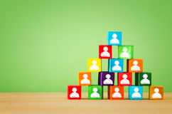Wood blocks pyramid with people icons, human resources and management concept. Image of a wood blocks pyramid with people icons over wooden table , human Royalty Free Stock Image
