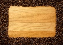 Wood board with coffee frame. Wooden background with coffee beans as frame Stock Photography