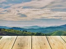 Wood board on mountain range in cloudy day. Wood board on mountain range in cloudy day, used for montage or display products among beautiful landscape Stock Image