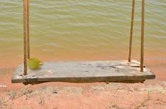 Wood board swing near the water Royalty Free Stock Photo