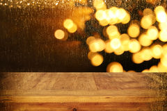 Wood board table in front of Christmas warm gold garland lights on wooden rustic background.  Royalty Free Stock Photography